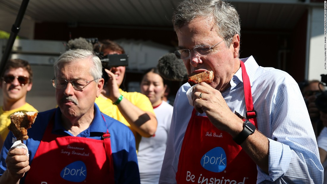 Bush and Branstad eat a pork chop on a stick on August 14.