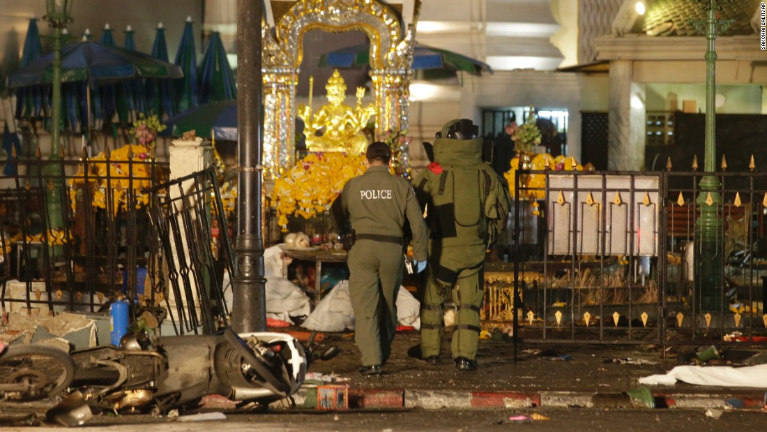 Police enter the Erawan Shrine after the explosion. The shrine sits at a busy intersection, with the city's Skytrain rumbling nearly overhead.