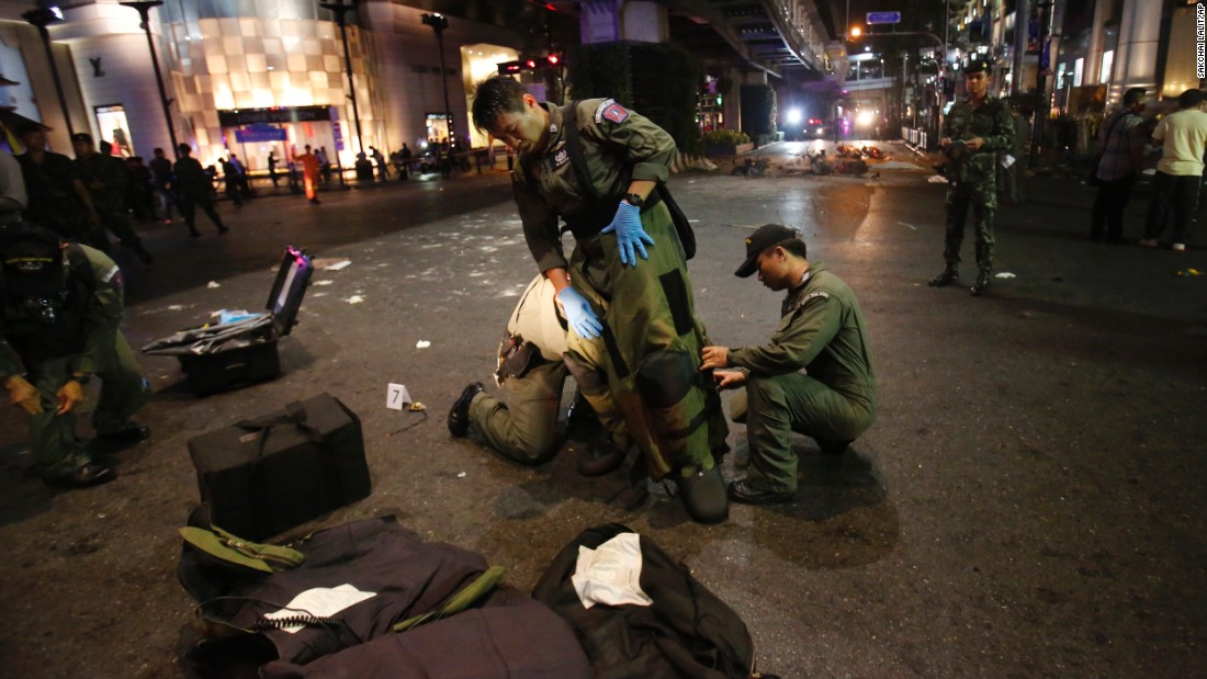 A bomb disposal team member suits up in the middle of an intersection after the blast.