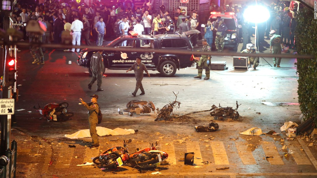 Police take photos at the scene of the explosion August 17. A bomb exploded in front of the shrine shortly after 7 p.m., a news report said.