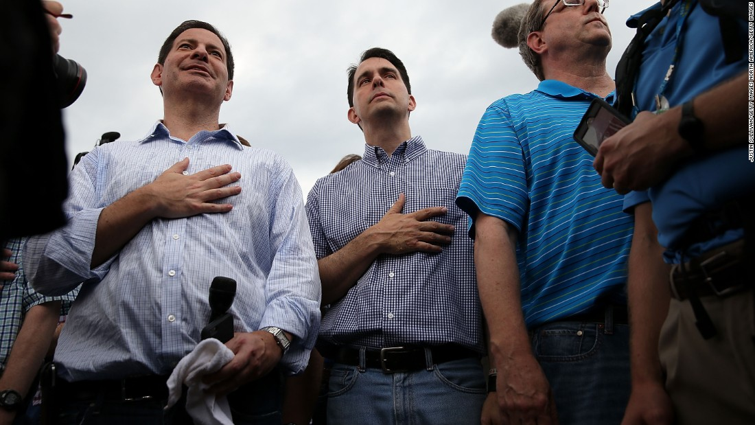 Walker, center, puts his hand over his heart as he watches a veterans parade on August 17.