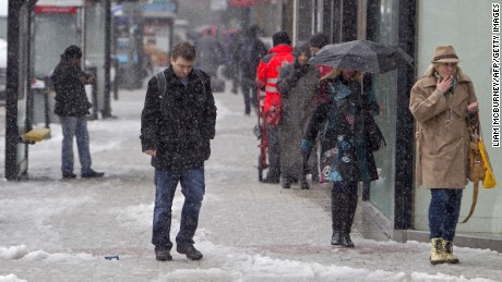 Pedestrians walk through the snow in Belfast City centre in Northern Ireland, on March 22, 2013. Britain should be celebrating the start of spring but the kingdom was shivering Friday after heavy snowfall left tens of thousands of homes without power. Northern Ireland bore the brunt of the cold snap, caused by an area of low pressure moving eastwards off the Atlantic Ocean.  AFP PHOTO / LIAM MCBURNEY        (Photo credit should read LIAM MCBURNEY/AFP/Getty Images)