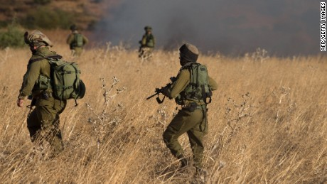 Israeli soldiers on Thursday inspect a field where rockets landed.
