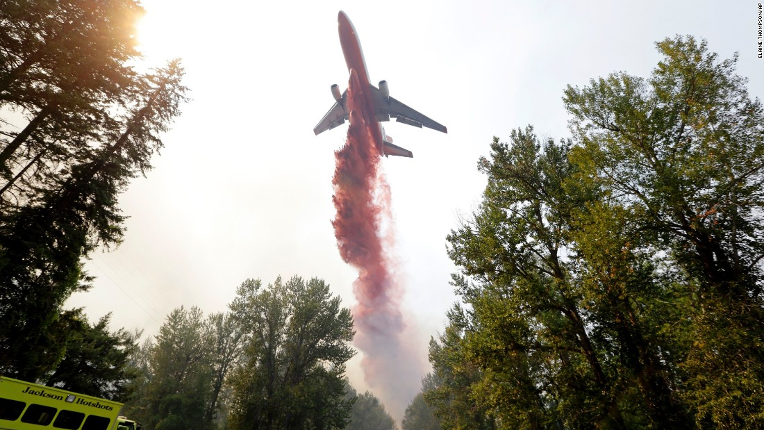 "A tanker drops fire retardant on a wildfire that flared up in Twisp on August 20. More than 100 wildfires were roaring throughout the state, according to Gov. Jay Inslee. ""I want to say this is an unprecedented cataclysm in our state,"" Inslee said. ""There are 390,000 acres burning. Last year was bad with 250,000 acres."""