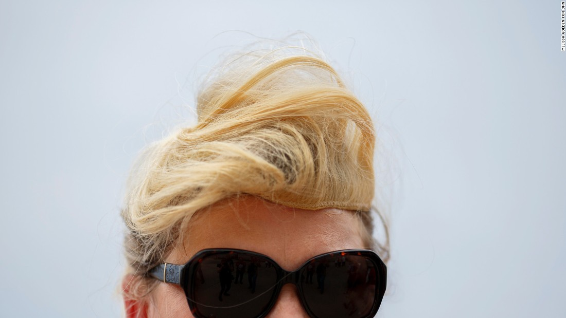 A Trump supporter wears a hairpiece similar to Trump's signature style.