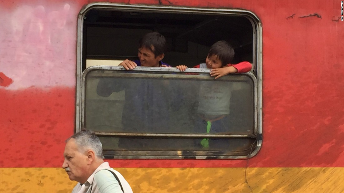 Father and son look out the window of a train in Macedonia.