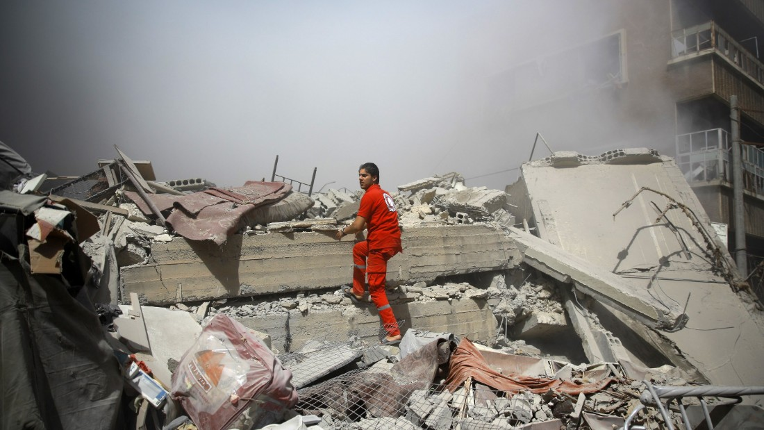 A member of the Syrian Red Crescent inspect rubble searching for victims in the rebel-held area of Douma, east of the capital Damascus, following shelling and air raids by Syrian government forces on August 22, 2015. At  least 20 civilians and wounded or trapped 200 in Douma, a monitoring group said, just six days after regime air strikes killed more than 100 people and sparked international condemnation of one of the bloodiest government attacks in Syria's war.   AFP PHOTO / ABD DOUMANY        (Photo credit should read ABD DOUMANY/AFP/Getty Images)