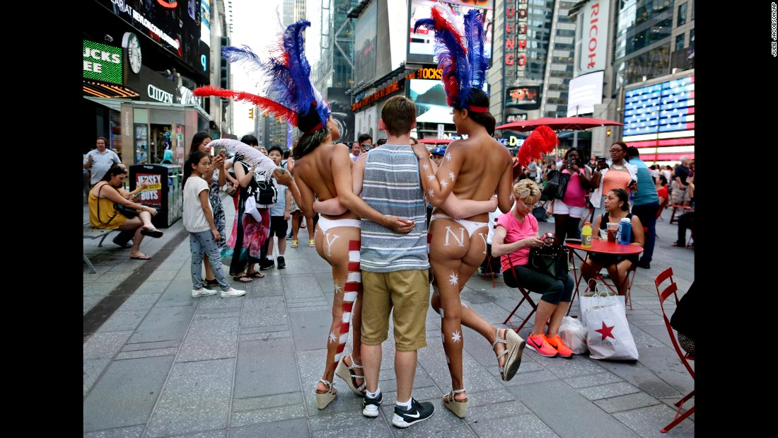 A tourist poses for a picture with two women on Tuesday, July 28.