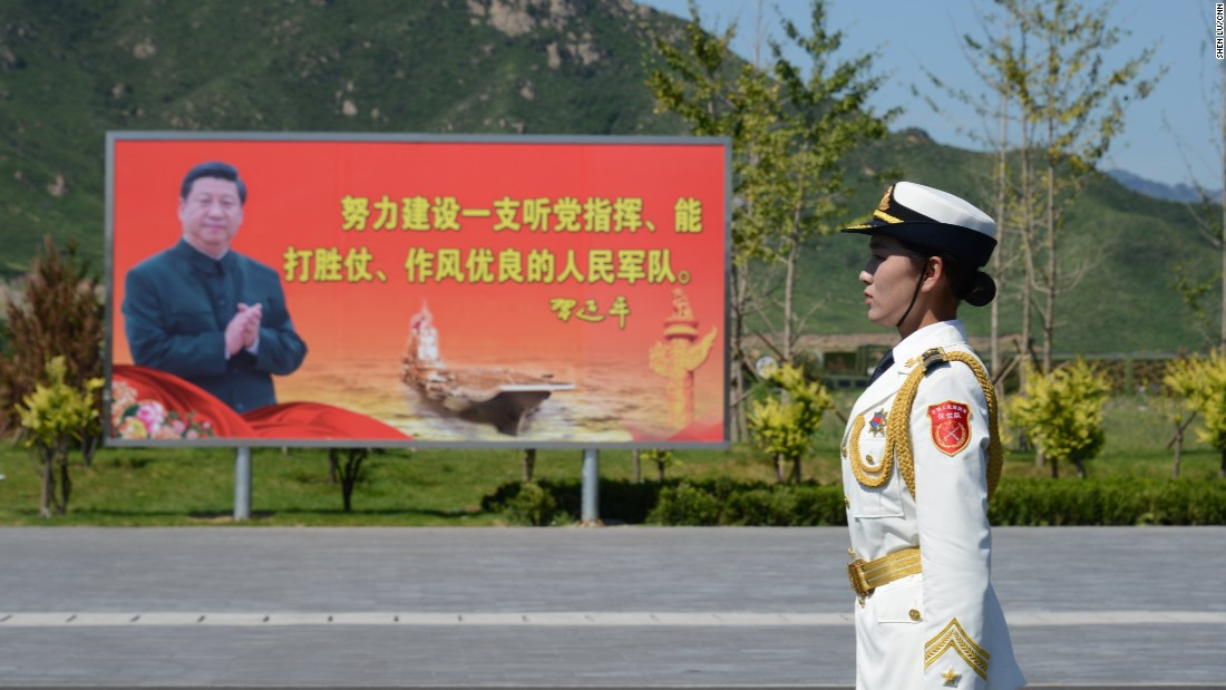 A female soldier stands in front of a billboard featuring Chinese president Xi Jinping on August 22.