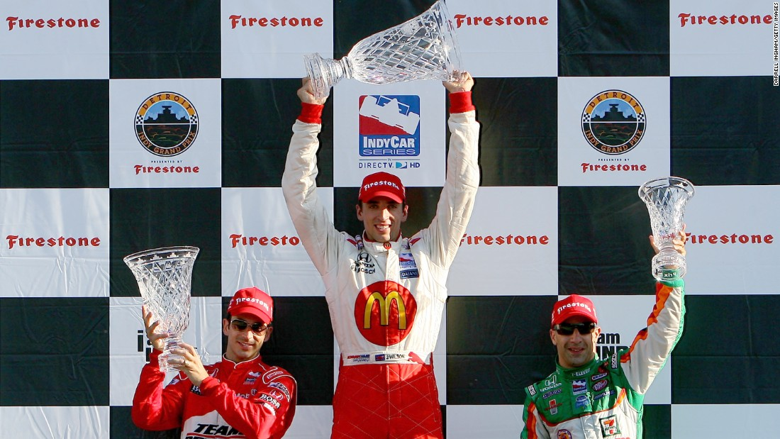 Wilson, center, celebrates an IndyCar win in August 2008.