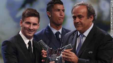 Messi receives his award from UEFA president Michel Platini, while rival Ronaldo looks away.
