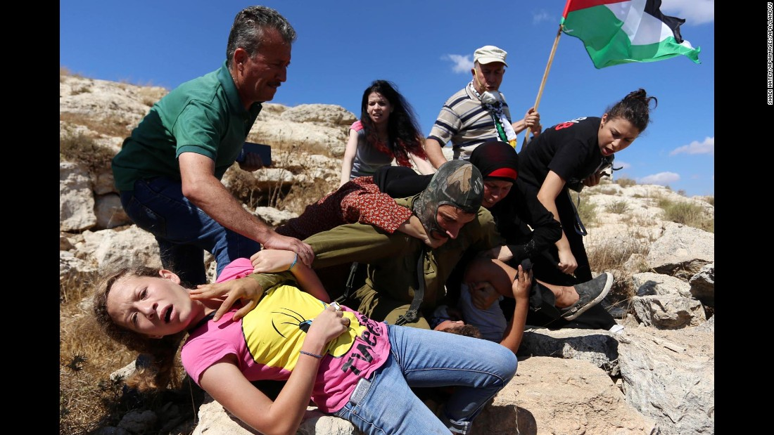 "The Israeli army defended its actions, saying that people in the crowd had thrown rocks at the soldiers. ""The forces decided to detain one of the Palestinians identified hurling rocks,"" an Israeli army spokeswoman told CNN. The army said the commander at the scene halted the arrest to avoid an escalation of the situation."