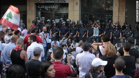 "Lebanese activists stand in front of riot police outside the environment ministry in downtown Beirut on September 1, 2015 as Lebanese police started forcefully evacuating protesters who had occupied part of the building in a surprise sit-in to demand the minister's resignation after mass protests which began over a nationwide trash collection crisis. A security source said police were gradually moving the several dozen protesters from the ""You Stink"" campaign down from the seventh floor of the building. AFP PHOTO / STRSTR/AFP/Getty Images"
