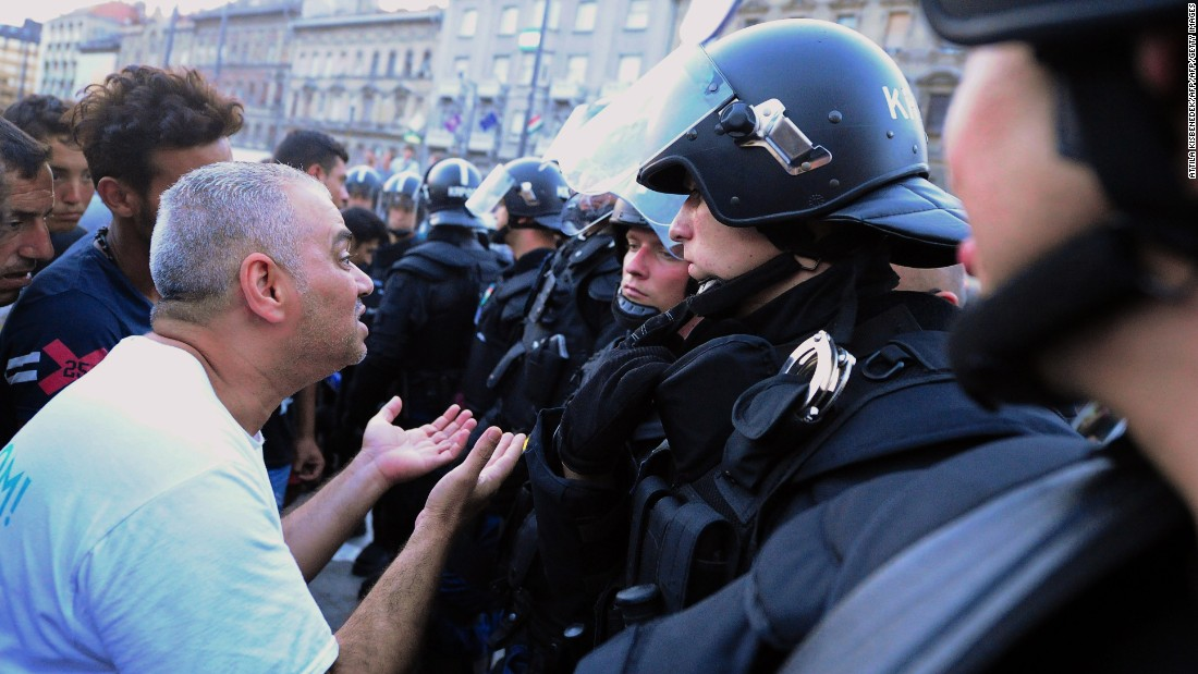 Refugees and migrants speak with riot police officers in front of Keleti station.