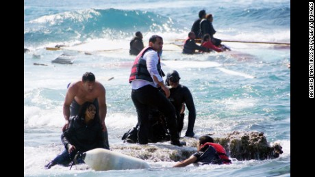 Rescue workers help a woman after a boat carrying migrants sank off the island of Rhodes, southeastern Greece.