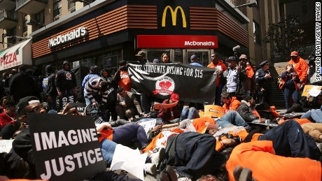 "NEW YORK, NY - APRIL 15:  Low wage workers, many in the fast-food industry, join with supporters for a ""die-in"" in front of a McDonald's to demand a minimum wage of $15 an hour on April 15, 2015 in New York City. In what organizers are calling the biggest ever mobilization of workers in the U.S., thousands of people took to the streets across the country to stage protests in front of businesses that are paying some of their workers the minimum wage. Home care workers, and employees at Walmart and fast food restaurants say that the current minimum is not a living wage.  (Photo by Spencer Platt/Getty Images)"