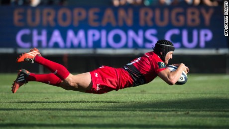 Toulon's fly-half Matt Giteau dives to score a try during the European Rugby Champions Cup match between Toulon and Llanelli Scarlets at the Mayol stadium in Toulon, southeastern France, on October 19, 2014. AFP PHOTO/BERTRAND LANGLOISBERTRAND LANGLOIS/AFP/Getty Images