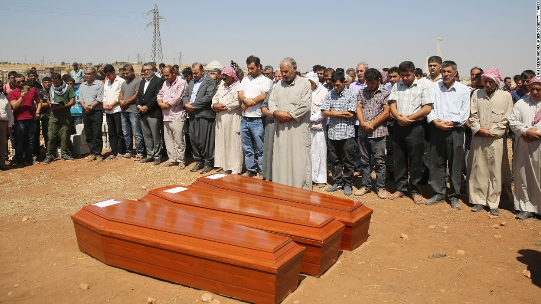 People stand near the coffins during the burial ceremony in Kobani on September 4, 2015.