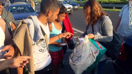 Ordinary Hungarians stop on the highway to hand out food and water to refugees.