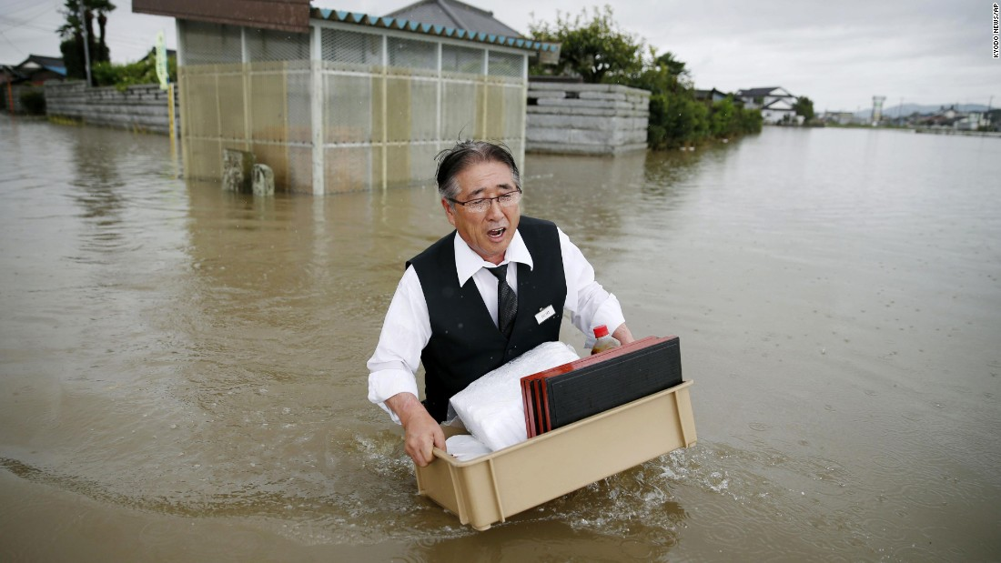 A man wades through a flooded street in Oyama, Japan, on Thursday, September 10, after heavy rain pounded the region for two straight days.