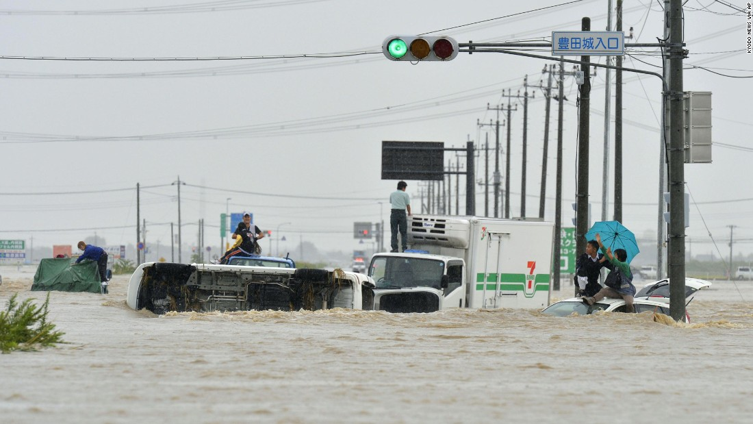 People await help while vehicles are overturned and submerged in Joso on September 10.