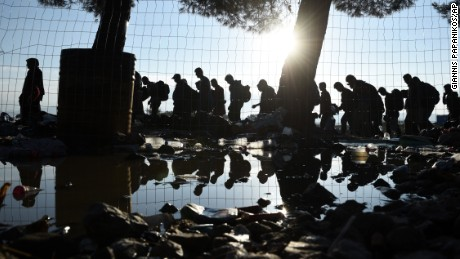 The sun rises as refugees and migrants walk to pass from the northern Greek village of Idomeni to southern Macedonia, Friday, Sept. 11, 2015. The sudden onset of autumn has taken tens of thousands by surprise all along the Balkans route from Greece to Hungary, the main gateway to Western Europe for more than 160,000 asylum seekers already this year. (AP Photo/Giannis Papanikos)