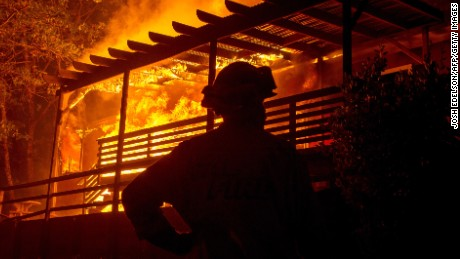 A firefighter looks on while a house is engulfed in flames during the Valley fire in Seigler Springs, California on September 13, 2015. The governor of California declared a state of emergency Sunday as raging wildfires spread in the northern part of the drought-ridden US state, forcing thousands to flee the flames. The town of Middletown, population 1,300, was particularly devastated by the Valley Fire, according to local daily Santa Rosa Press-Democrat, which said the fire grew from 50 acres to 10,000 over just five hours Saturday -- before quadrupling in size overnight. AFP PHOTO/JOSH EDELSON        (Photo credit should read Josh Edelson/AFP/Getty Images)