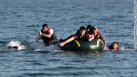 Syrian migrants paddle their dinghy to the shores of the Greek island of Kos on August 17, 2015 after their small engine broke down as they motored across the sea from Turkey. Authorities on the island of Kos have been so overwhelmed that the government sent a ferry to serve as a temporary centre to issue travel documents to Syrian refugees -- among some 7,000 migrants stranded on the island of about 30,000 people. The early hours are the safest time for migrants travelling from Turkey to the Greek islands just across the water, which have seen a huge influx of refugees escaping the civil war in Syria and chaos in Afghanistan since the beginning of this year..