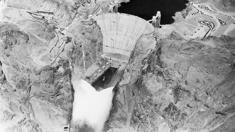 12 Sep 1936, USA --- Original caption: 9/12/1936-Boulder Dam, AZ/NV- An electrical impulse released by President Roosevelt pressing a button across the continent sent 3,600,000 cubic feet of water a minute tumbling through Gigantic Boulder Dam, and put the Colorado River to work generating electrical power. This photo made by Albert Kopec from a Richfield Oil Company plane, shows the Niagara of water from the 12 outlets; six on the Nevada side and six on the Arizona side. --- Image by © Bettmann/CORBIS