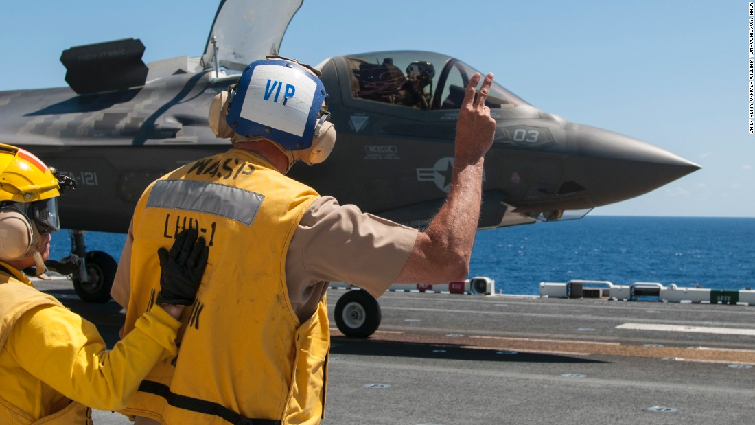 Vice Adm. William Hilrides, commander of Naval Sea Systems Command, holds up two fingers to indicate to the F-35B Lightning II pilot to power up for takeoff aboard the amphibious assault ship the amphibious assault ship USS Wasp in May.