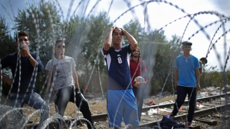 Migrants demonstrate with police officers through the razor wire fence from the Serbian side of the Serbian-Hungarian border at the closed rail track crossing point on September 15, 2015 in Roszke, Hungary.