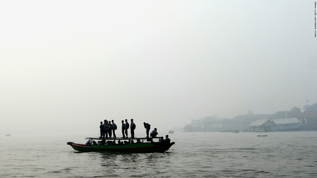 Students cross a river under a blanket of haze September 17 in Palembang, Indonesia.