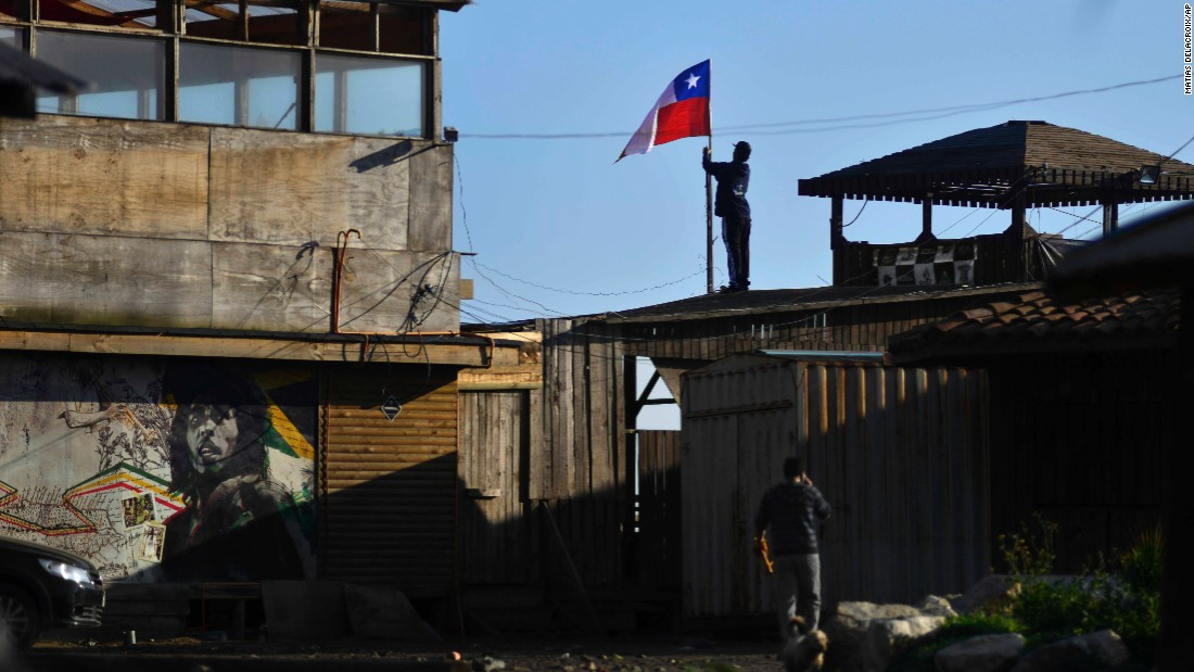 A man secures a Chilean flag on a roof in Concon, Chile, after tsunami waves triggered by a 8.3-magnitude earthquake damaged homes and businesses on Thursday, September 17. Several coastal towns were flooded.