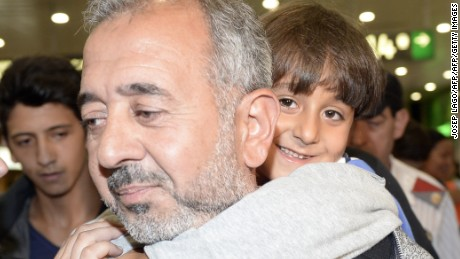 Osama Abdul Mohsen (C), the Syrian refugee who made world headlines when a Hungarian journalist tripped him over as he fled, and his son Zaid (R) arrive at Barcelona, on September 16, 2015,  prior to leaving again for Madrid. The Spanish football coaching school CENAFE, in the Madrid suburb of Getafe said today  it is giving a job to Osama Abdul Mohsen, former manager of Syrian first division side Al-Fotuwa. Video footage of journalist Petra Laszlo tripping Mohsen onto the grass as he ran with his son Zaid in his arms near the Hungary-Serbia border sparked outrage this month. She was fired from the television channel she worked for. AFP PHOTO / JOSEP LAGO        (Photo credit should read JOSEP LAGO/AFP/Getty Images)
