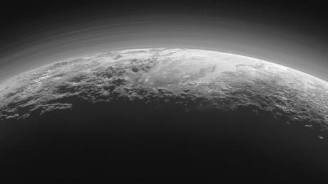 Just 15 minutes after its closest approach to Pluto on July 14, 2015, NASA's New Horizons spacecraft looked back toward the sun and captured this near-sunset view of the rugged, icy mountains and flat ice plains extending to Pluto's horizon. The smooth expanse of the informally named icy plain Sputnik Planum (right) is flanked to the west (left) by rugged mountains up to 11,000 feet (3,500 meters) high, including the informally named Norgay Montes in the foreground and Hillary Montes on the skyline. To the right, east of Sputnik, rougher terrain is cut by apparent glaciers. The backlighting highlights more than a dozen layers of haze in Pluto's tenuous but distended atmosphere. The image was taken from a distance of 11,000 miles (18,000 kilometers) to Pluto; the scene is 780 miles (1,250 kilometers) wide.