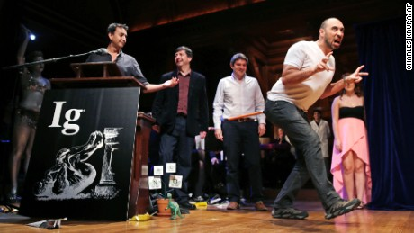 Bruno Grossi, a researcher from Chile, shows how a chicken would walk like a dinosaur with a weighted stick attached to its tail, while being honored with an Ig Nobel Prize on Thursday, September 17, 2015.