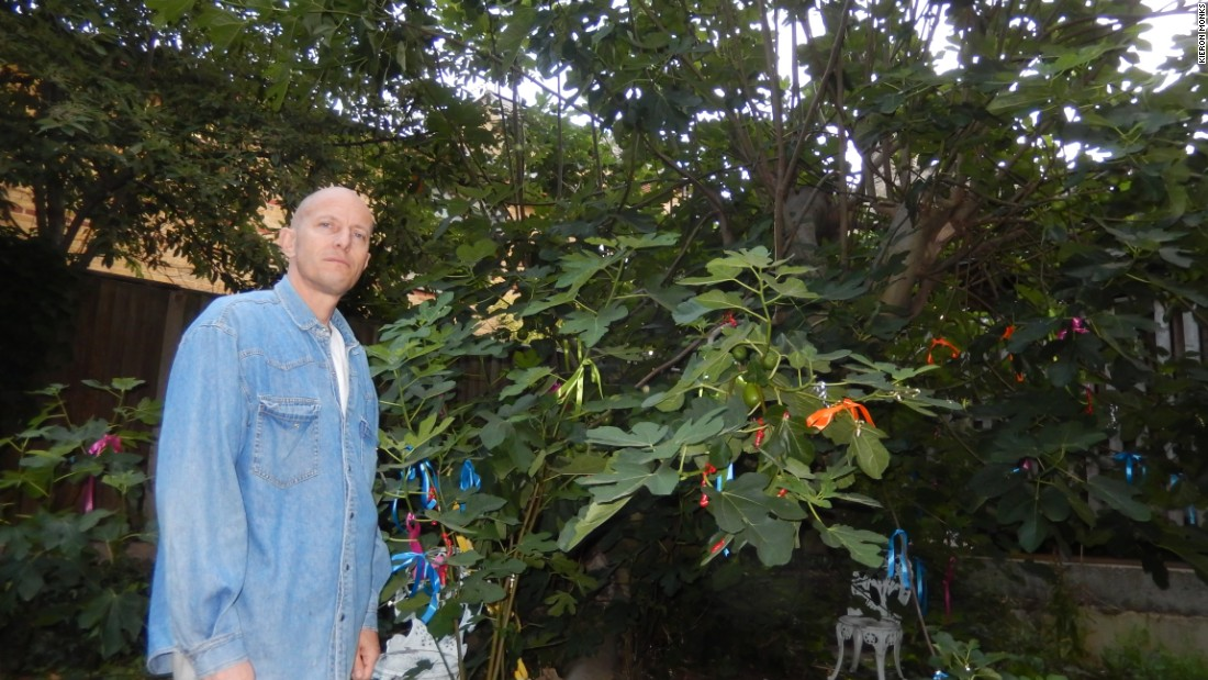 Peter Keserue with the community's fig tree, which he maintains and harvests.