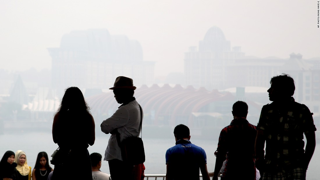 Thick air pollution has been choking parts of Indonesia, Singapore and Malaysia for weeks. People are silhouetted against Singapore's popular tourist destination, Sentosa, seen through the haze on September 24, 2015.