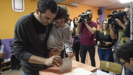 A man with his daugther casts his ballot for the regional election at a polling station in Barcelona on September 27, 2015. After an emotional climax to campaigning on September 25, Catalans headed to the polls today for an election dubbed the most important in Spain's recent history, with polls pointing to a win by separatists who are vowing to declare the region independent. AFP PHOTO / JOSEP LAGO        (Photo credit should read JOSEP LAGO/AFP/Getty Images)