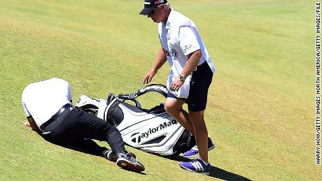 UNIVERSITY PLACE, WA - JUNE 19:  Jason Day of Australia is tended to by caddie Colin Swatton as he lays on the ninth green after falling due to dizziness during the second round of the 115th U.S. Open Championship at Chambers Bay on June 19, 2015 in University Place, Washington.  (Photo by Harry How/Getty Images)