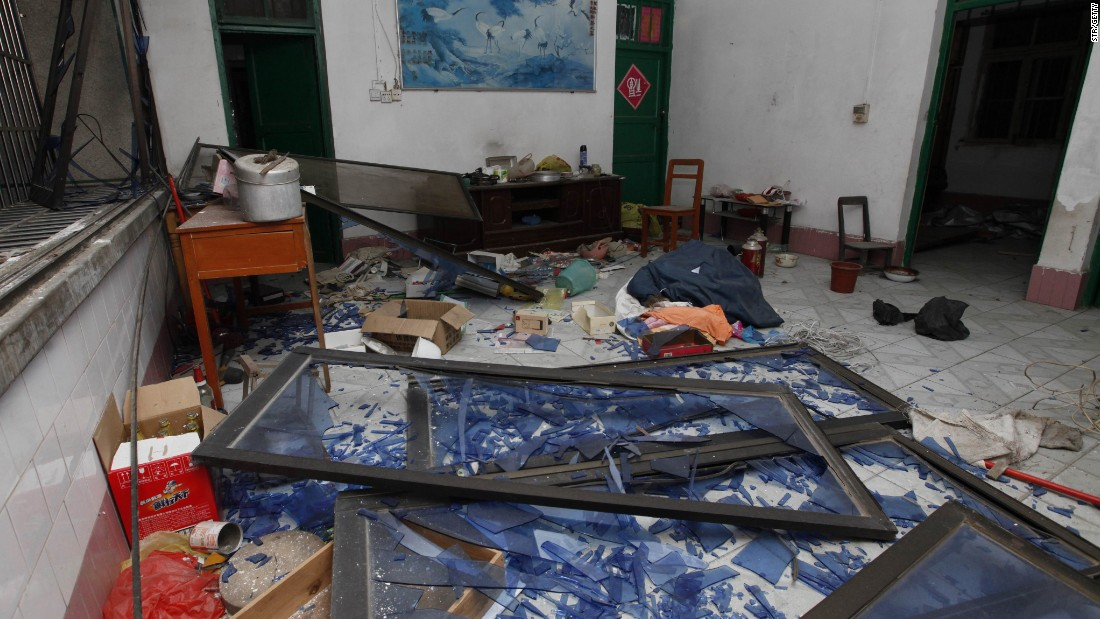Damaged windows, debris and shattered glass are seen in a room that was hit by the explosion.