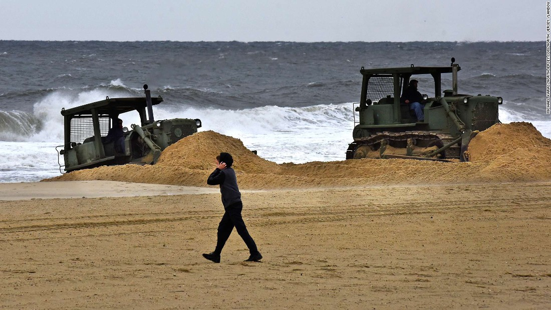 A boy walks on a beach in Belmar, New Jersey, on October 1, as front loaders build sand dunes in preparation for Hurricane Joaquin.