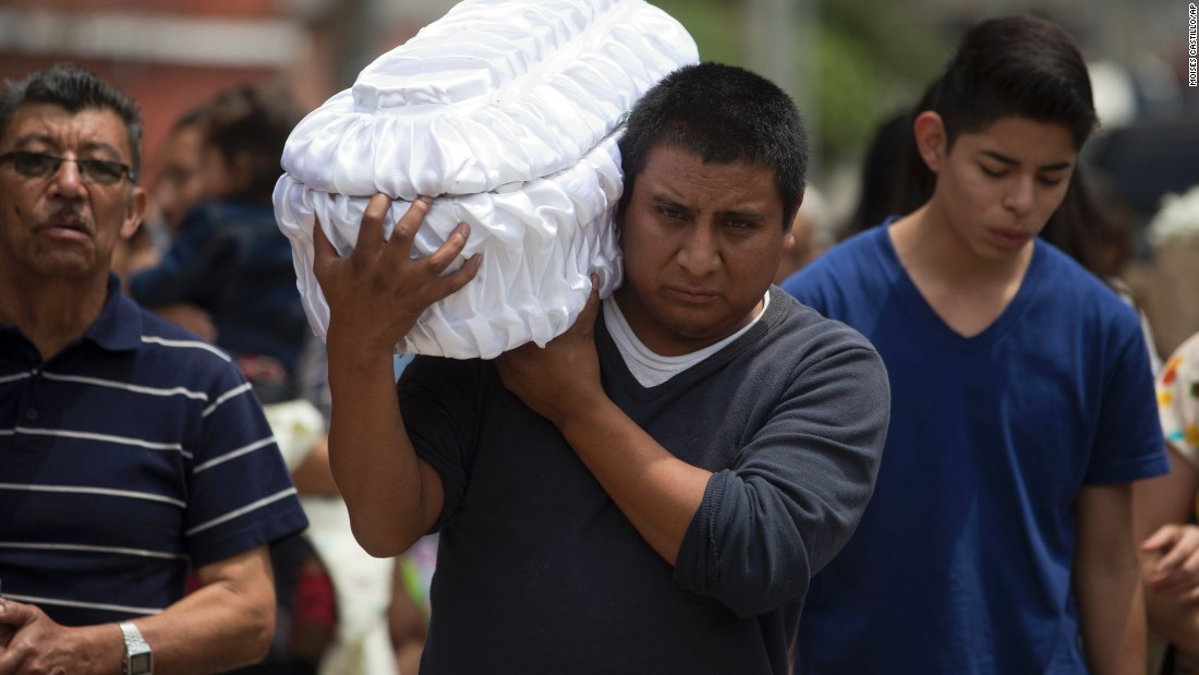 Welsar Nazario carries the coffin of his 5-month-old nephew Alezandro Macario, who died in a mudslide, to the Santa Catarina Pinula cemetery on the outskirts of Guatemala City on October 3.
