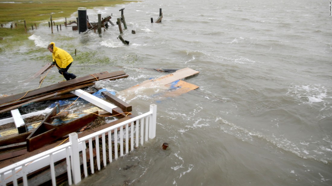 Stuart Tait ties together wood after his house collapsed into an inlet  on Grassy Sound during high tide on October 3 north of North Wildwood, New Jersey.