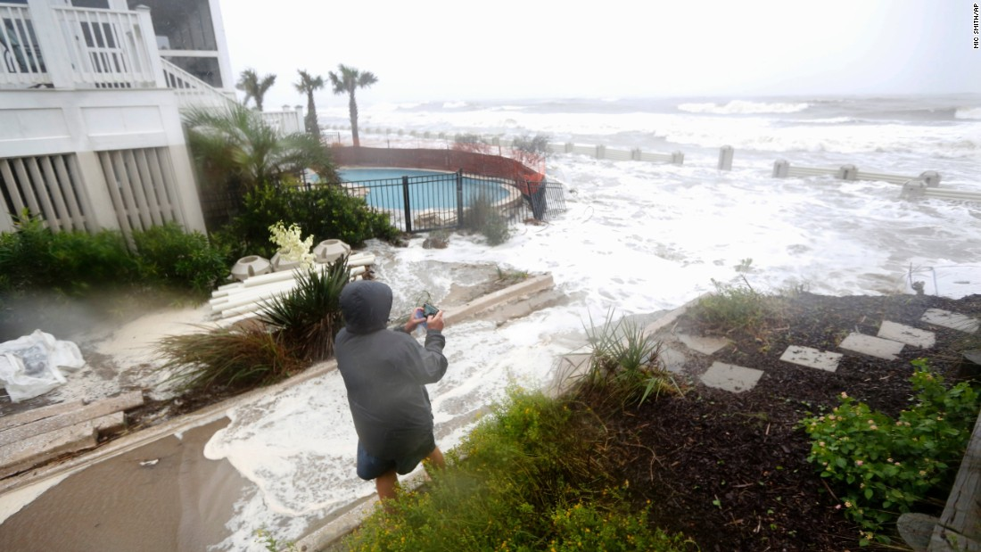 Bob Ashbaugh, from Pittsburgh, takes video of waves crashing over homes at risk from erosion during high tide in Isle of Palms, South Carolina, on October 3.