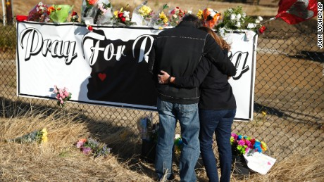 Two people embrace as they place flowers at a makeshift memorial near the road leading to Umpqua Community College