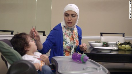 Sama Keichour feeds her baby daughter.