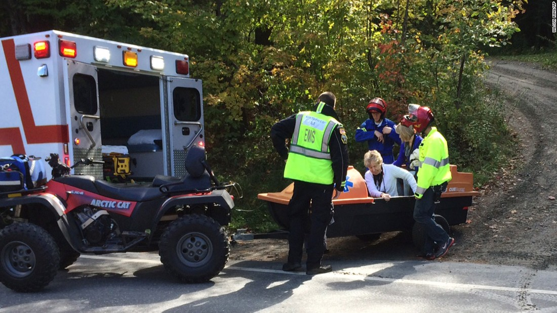 Emergency first responders assist a woman as she is transferred to an ambulance.
