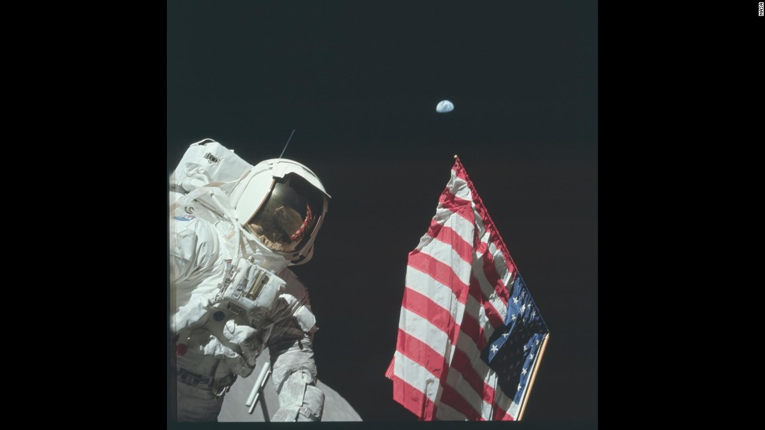 Astronaut Harrison Schmitt is photographed next to the American flag while walking on the moon during Apollo 17.