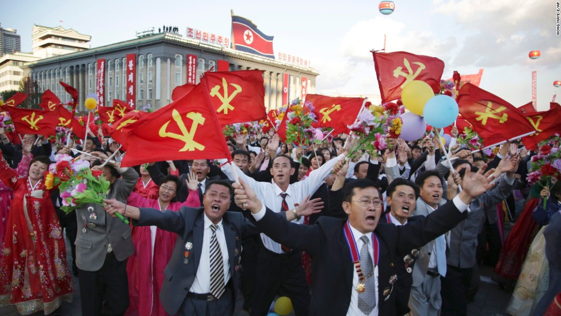 North Koreans parade with flags of the ruling Workers' Party.